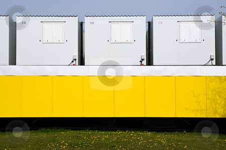 Construction stock photo, Security boarding and small builders huts by a new development, by Paul Phillips