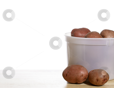 Organic Potatoes stock photo, A pail of fresh organic garden red potatoes, shot on a wooden table with a solid white background by Richard Nelson