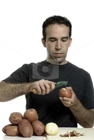 Man Peeling Potatoes stock photo, Young man peeling potatoes with a potato peeler, isolated against a white background by Richard Nelson