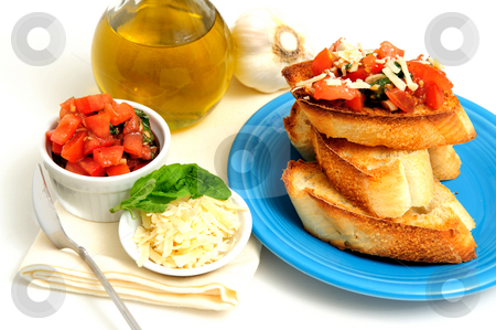 Bruschetta With Olive Oil stock photo, Bruschetta on a turquoise plate with toasted baguette slices and more tomato, basil, garlic and olive oil including grated asiago cheese in a small white containers by Lynn Bendickson