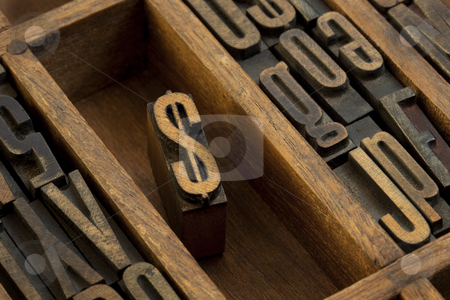 Dollar - vintage letterpress wooden type stock photo, Financial or monetary concept,  dollar symbol - vintage letterpress wooden type (condensed gothic) in old printer drawer among other letters stained by dark ink by Marek Uliasz