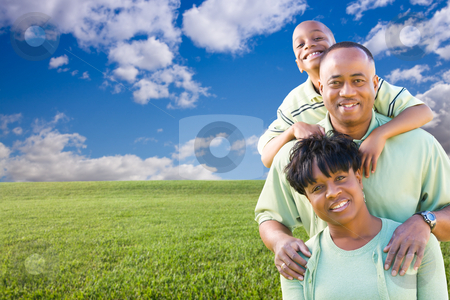 Happy Family Over Grass Field, Clouds and Sky stock photo, Happy African American Family Over Grass Field, Clouds and Blue Sky - Room For Your Own Text to the Left. by Andy Dean