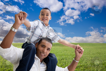 Father and Son Over Grass Field, Clouds and Sky stock photo, Happy Hispanic Father and Son Over Grass Field, Clouds and Blue Sky. by Andy Dean