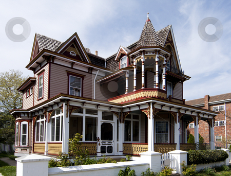 Colorful Victorian style house stock photo, Beautiful colorful wooden Victorian style residential building with porch and balcony on a bright summer spring day. by Paul Hakimata