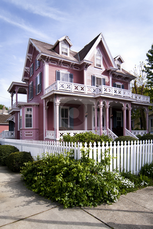 Pink Victorian house stock photo, Beautiful pink Victorian house with porch and balcony surrounded by a white picked fence. by Paul Hakimata