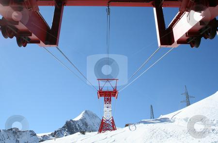Ski lift on snowy mountain stock photo, Underside of ski lift and pylons on snowy mountain in Alps, Switzerland. by Martin Crowdy