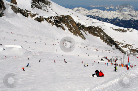 Skiers on Alpine slope stock photo, Scenic view of skiers on Alpine ski slope with mountains in background, Switzerland. by Martin Crowdy