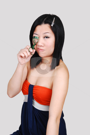 Chinese Girl doing eyelashes. stock photo, A young pretty Asian woman fixing her eyelashes, in a shoulder free dress, sitting in the studio for light gray background. by Horst Petzold