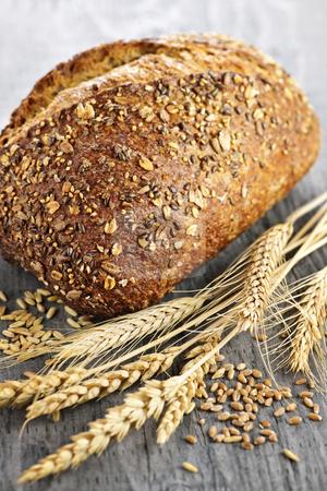 Loaf of multigrain bread stock photo, Loaf of fresh baked multigrain bread with grain ears by Elena Elisseeva