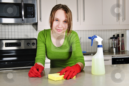 Young woman cleaning kitchen stock photo, Young woman doing kitchen cleaning chores with rubber gloves by Elena Elisseeva