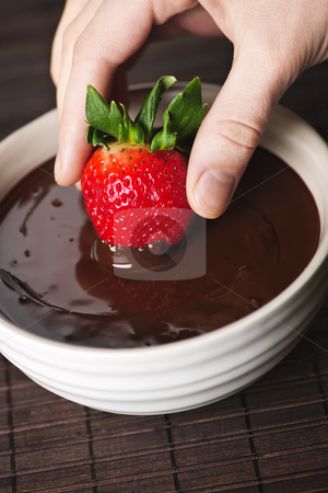 Hand dipping strawberry in chocolate stock photo, Hand dipping fresh strawberry in melted chocolate by Elena Elisseeva