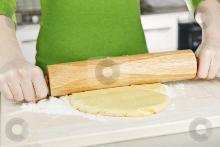 Hands with rolling pin and cookie dough stock photo, Spreading out cookie dough with wooden rolling pin by Elena Elisseeva
