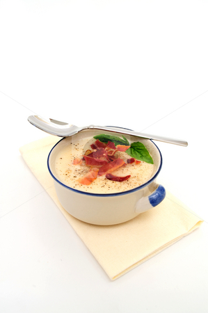 Cream Of Potato Soup stock photo, Potato soup topped with crisp bacon and fresh Basil leaves served in a rustic blue and white bowl by Lynn Bendickson
