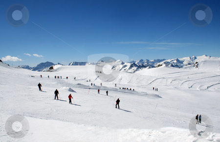 Skiers on Alpine ski slope stock photo, Scenic view of group of skiers on Alpine ski slope with blue sky background. by Martin Crowdy