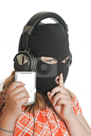Illegal MP3 Downloads stock photo, Closeup view of a young girl wearing a ski mask, listening to illegal music, isolated against a white background. by Richard Nelson