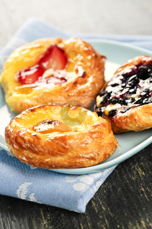 Three fruit danishes stock photo, Closeup of three fruit danish desserts on a plate by Elena Elisseeva