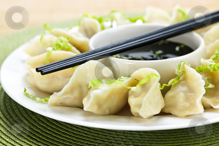 Steamed dumplings and soy sauce stock photo, Closeup on plate of steamed dumplings with soy sauce and chopsticks by Elena Elisseeva