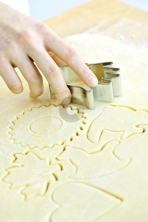 Cookie cutter and dough stock photo, Cutting cookie shapes in rolled dough with cutter by Elena Elisseeva