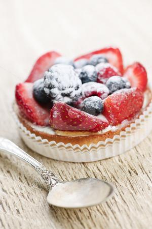 Fruit tart with spoon stock photo, Fancy gourmet fresh fruit dessert tart with spoon by Elena Elisseeva