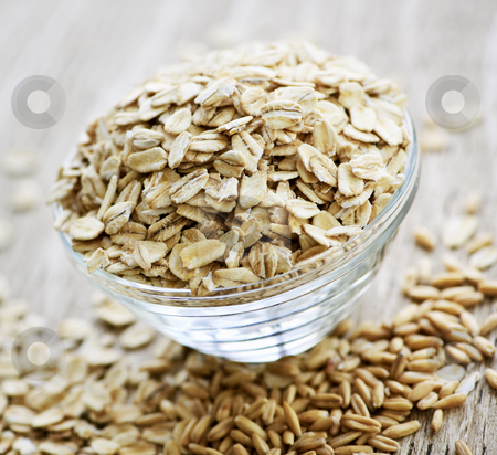 Bowl of uncooked rolled oats stock photo, Nutritious rolled oats heaped in a glass bowl by Elena Elisseeva