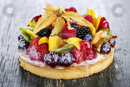 Mixed tropical fruit tart stock photo, Fresh dessert fruit tart covered in assorted tropical fruits by Elena Elisseeva