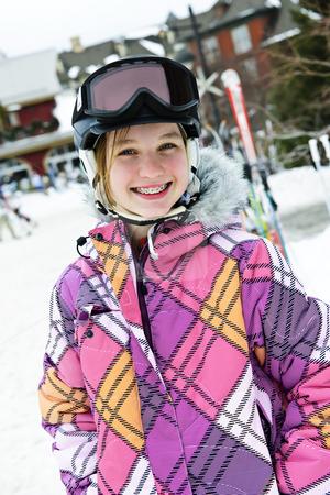 Happy girl in ski helmet at winter resort stock photo, Portrait of happy teenage girl in ski helmet and goggles at winter resort by Elena Elisseeva