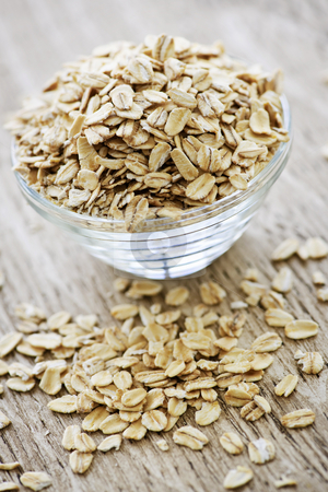 Bowl of raw rolled oats stock photo, Nutritious rolled oats heaped in a glass bowl by Elena Elisseeva