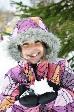 Happy winter girl holding snow stock photo, Portrait of happy teenage girl holding snow in gloves by Elena Elisseeva