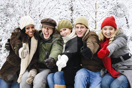 Group of friends outside in winter stock photo, Group of diverse young friends showing thumbs up outdoors in winter by Elena Elisseeva