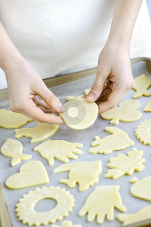 Baking sheet with cookies stock photo, Chef placing cutout cookie dough shapes on tray for baking by Elena Elisseeva