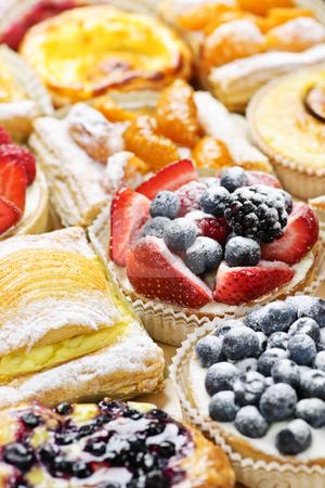 Assorted tarts and pastries stock photo, Background of assorted fresh sweet tarts and pastries by Elena Elisseeva