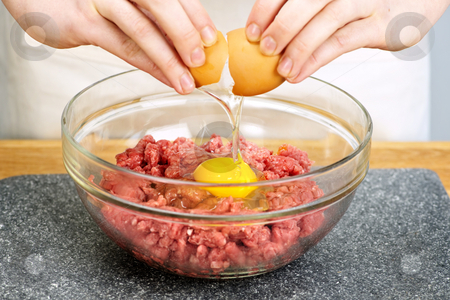 Cooking with egg and ground beef stock photo, Chef cracking egg into bowl of ground beef by Elena Elisseeva
