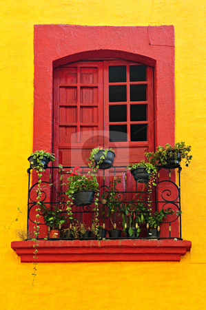 Window on Mexican house stock photo, Red painted window with plants and wrought iron railing in Mexico by Elena Elisseeva