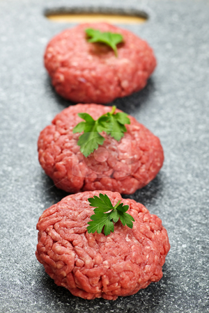 Hamburger patties stock photo, Three ground beef hamburger patties on cutting board by Elena Elisseeva