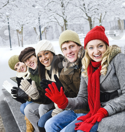 Group of friends outside in winter stock photo, Group of diverse young friends waving hello outdoors in winter by Elena Elisseeva