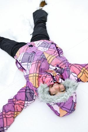 Girl making snow angel stock photo, Happy teenage girl making snow angel in winter by Elena Elisseeva