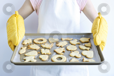Freshly baked cookies stock photo, Woman holding fresh baked homemade shortbread cookies on cookie tray by Elena Elisseeva