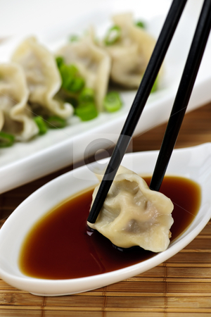 Steamed dumplings and soy sauce stock photo, Dumpling being dipped in soy sauce with chopsticks by Elena Elisseeva