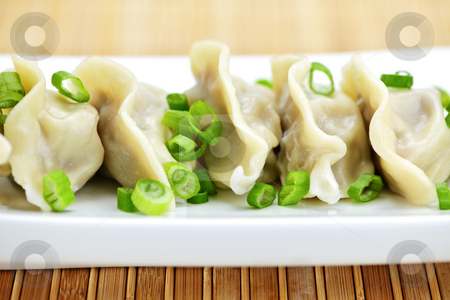 Plate of dumplings stock photo, Plate of cooked chinese dumplings in a row by Elena Elisseeva