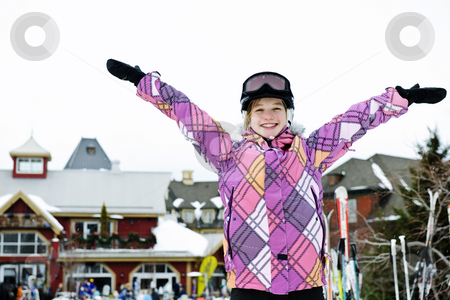 Happy girl with arms raised at resort stock photo, Happy teenage girl with arms raised in ski helmet at winter resort by Elena Elisseeva