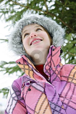 Happy young girl in winter jacket stock photo, Portrait of happy teenage girl in winter ski jacket looking up by Elena Elisseeva
