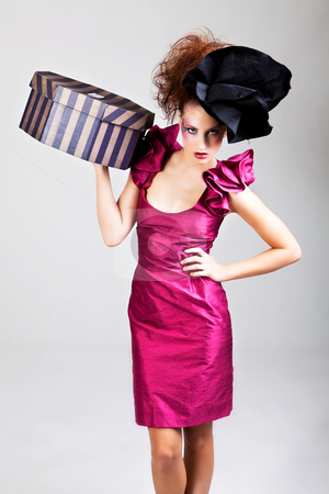 Young Woman in Avant Garde Attire stock photo, A young woman dressed in avant garde attire and carrying a hat box. She is wearing a hat and has cosmetic artwork on her right temple. Vertical shot. by Angela Hawkey