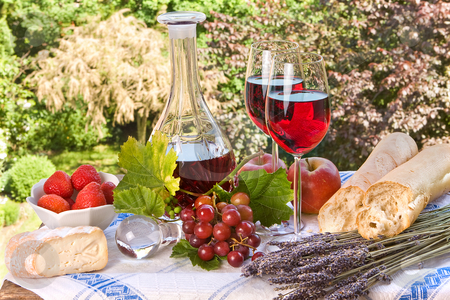 Happy picnic stock photo, Country-style setting with wine, fruit, bread and cheese by Anneke
