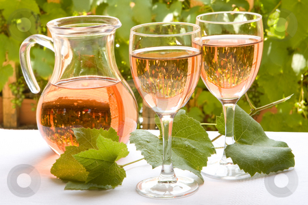 French rose wine stock photo, Two glasses of french rose wine against a background of grapevines by Anneke