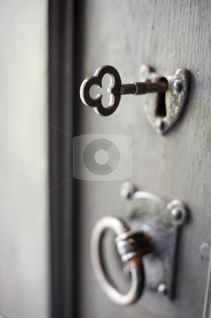 Antique lock and key stock photo, An metal key inserted into an old door pictured with a narrow depth of field by Stephen Gibson