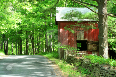 Red barn in the woods stock photo, A Red barn in the woods near a road by Jim Mills