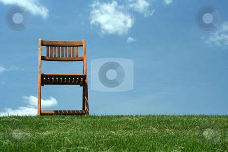 Wooden chair on a hilltop stock photo, A Wooden chair with grass and sky by Jim Mills