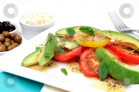 Avocado And Tomato Salad stock photo, Red and yellow sliced tomatoes with  avocado, fresh oregano leaves with an olive oil and raspberry vinaigrette dressing on a square white plate with green and black olives in small bowls by Lynn Bendickson