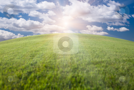 Green Grass Field, Blue Sky and Sun stock photo, Arched Horizon of Lush Green Grass Field, Blue Sky with Clouds and Sun. by Andy Dean