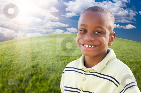 Handsome African American Boy Over Grass and Sky stock photo, Handsome African American Boy Over Clouds, Sky and Arched Horizon of Grass Field. by Andy Dean